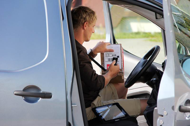 Man scanning parcel in the front of a van.